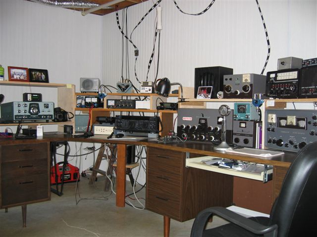 Fred's shack . L-shaped with HW-100 on the left and and old VIking 2, Hammarlund receiver, and Drake 2-B receiver.